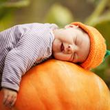 Kleinkind schläft auf großem Kürbis © Aliaksei Lasevich